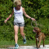 "Joplin Humane Society volunteer Kelly Johnson takes a jog with ""Tebow,"" a male pitbull. at the Joplin Humane Society on Tuesday.<br /> Globe 