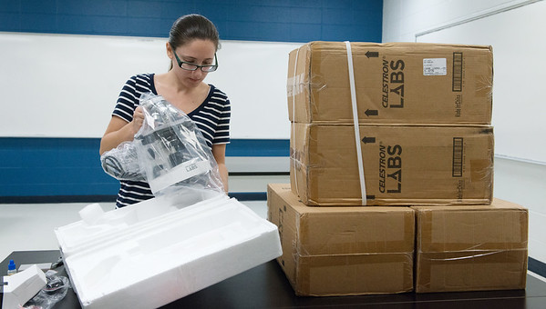 Alicia Abruzzo, science teacher at McAuley High School, prepares a microscope for Project Lead the Way on Aug. 9.<br /> Globe | Roger Nomer