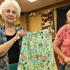 Dorothy Shull holds one of the more festively colored skirts to be shipped to girls in a Haitian orphanage on Thursday at First United Methodist Church in Carthage as Virginia Gray looks on. The skirts were sewn by about two dozen volunteers.<br /> Globe | Laurie SIsk