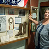 Michele Hansford talks about a pair of boots from the Juvenile Shoe Factory, listed on a new digital history map of Carthage, during an interview on Wednesday at the Powers Museum.<br /> Globe | Roger Nomer