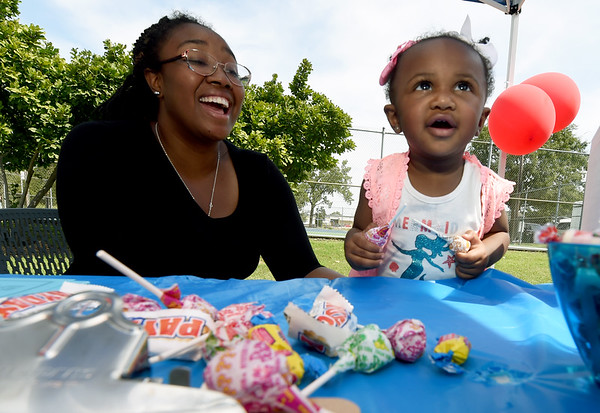 One-year-old Sage Fulgham greets visitors with free suckers as her mother, Shonte Fulgham looks on at their Family Heritage booth during Park Days on Saturday at Ewert Park.<br /> Globe | Laurie Sisk
