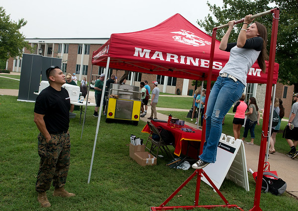 Staff Sgt. Ray Muro, officer selection assistant for the US Marine Corp., encourages Anna McNeil, a Missouri Southern freshman from Indianola, Ok., as she does pullups on Wednesday at Community Day at MSSU.<br /> Globe | Roger Nomer