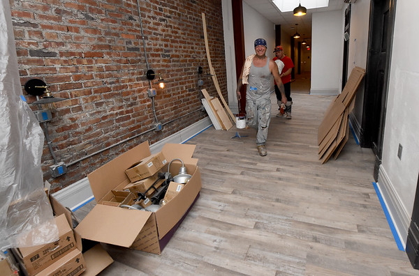 Workers walk inside a hallway of the Commerce Building as they ready apartments for students on Tuesday in downtown Pittsburg.<br /> Globe | Laurie Sisk