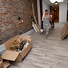Workers walk inside a hallway of the Commerce Building as they ready apartments for students on Tuesday in downtown Pittsburg.<br /> Globe   Laurie Sisk