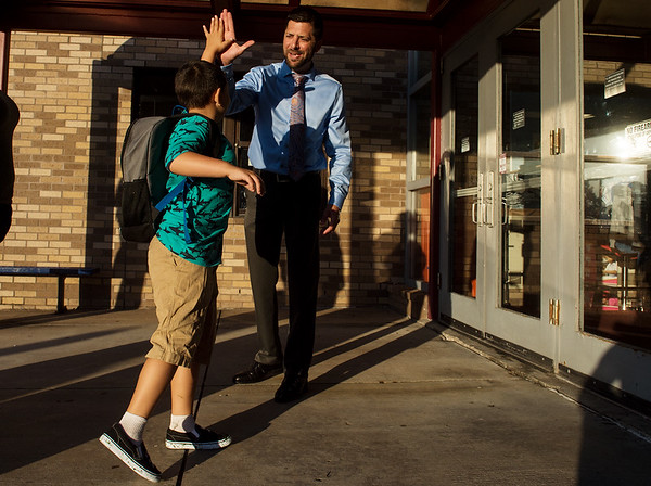 Gabe Inman, a second grader at Cecil Floyd Elementary, gives a high five to his principal Chris Bozarth before school on Thursday.<br /> Globe | Roger Nomer