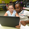 From the lef: Nine-year-olds Desi Knoderer and Amitiona Warren share an iPad during Power Hour at the Boys and Girls Clubs of Southwest Missouri's After School Program on Thursday. Power Hour affords kids the opportunity to do homework, learn science and otherwise augment their studies.<br /> Globe | Laurie Sisk