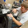 Chris Gulley disassembles a cart at Joplin Workshops on Friday.<br /> Globe | Roger Nomer