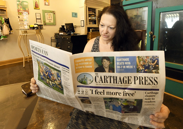 Longtime Carthage Press reader and advertiser Tiffany Goad, owner of Bloom Boutique, reads the final edition of The Carthage Press on Wednesday.<br /> Globe | Laurie Sisk