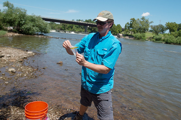 James Whitney, assistant professor of biology at Pittsburg State University, prepares sample bags at Spring River in Baxter Springs on Thursday.<br /> Globe | Roger Nomer