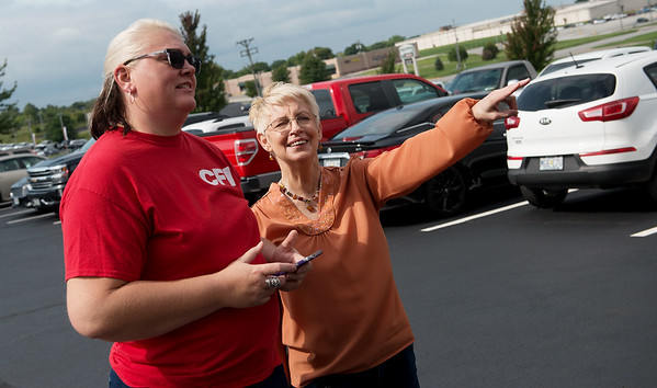 Jessica Vandaveer, senior customer service at CFI, left, and Debbi Tobiaz, CFI permit department worker, check out a truck honoring female drivers on Tuesday at CFI.<br /> Globe | Roger Nomer