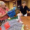 From the left: Virginia Gray and Carol McCombs fold and pack skirts to be shipped to girls in a Haitian orphanage on Thursday at First United Methodist Church in Carthage. The skirts were sewn by about two dozen volunteers.<br /> Globe | Laurie SIsk