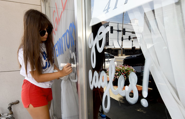 "Joplin Hgh School cheerleader Emily Garcia joins other members of the JHS cheer and dance squads as they ""Paint the Town"" on Friday in downtown Joplin. Members of both squads hope to start a tradition of painting the windows of downtown businesses in support of the Eagles.<br /> Globe 
