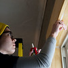 Claire Johnson, College Heights senior, caulks a window on Monday at God's Resort.<br /> Globe | Roger Nomer
