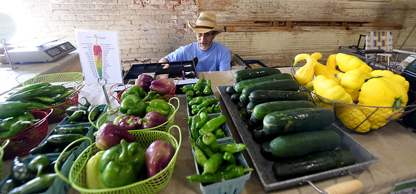 Granby farmer Doug Scott, of Oakwoods Farm, restocks produce at his colorful stand inside the Empire Market on Saturday.<br /> Globe | Laurie Sisk