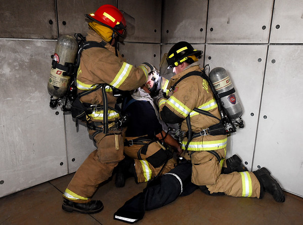 Joplin firefighters Rob Johnson, left, and Levi McBryde, right, assist comrade Justin Slates during drills to help rescue downed firefighters during training drills on Thursday at the Joplin Public Safety Training Center.<br /> Globe | Laurie Sisk