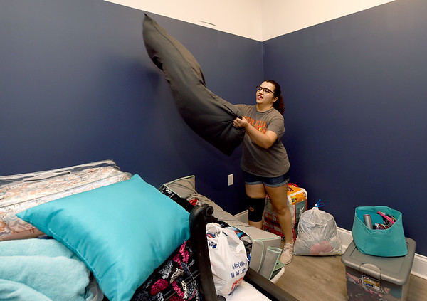Olathe junior Allison Rangel begins to organize her bedroom in the Opera House in the Block22 project in downtown Pittsburg on Saturday. As a former band member, Rangel said she was delighted to have been assigned the John Philip Sousa apartment.<br /> Globe | Laurie Sisk