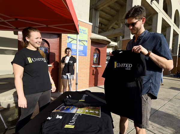 Spencer Layne, right, gets a United at the Stadium shirt from Kenzie Zar, of Advanced Family Medicine, during a suicide prevention event on Wednesday night at Junge Stadium. The event featured games, food, informational booths and speakers.<br /> Globe | Laurie Sisk