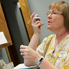 Linda Flory demonstrates an asthma inhaler on Thursday at the Joplin Community Clinic.<br /> Globe | Roger Nomer