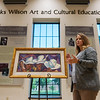 "Jennifer Walker, executive director of the NEO Development Foundation, talks about the Charles Banks Wilson painting ""White Hats"" on Friday at NEO.<br /> Globe 