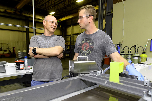 From the left: Quality Lead Mike Loveless talks to Production Tech Daniel Elliott at the cathode casting section of ZAF Energy Systems on Thursday at ZAF. The company is one of several in the area who plan to expand their workforces.<br /> Globe | Laurie SIsk
