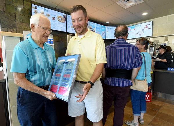 From the left: Allen Shirley, president of the Joplin Historical Society, presents framed Dairy Queen Home-Paks from the 1950s on behalf of the the Joplin Museum Complex to new Dairy Queen owner Evan Juline on Thursday at the restaurant. The bags harken back to a time before air conditioning in cars, when customers needed to keep their DQ product cold until they reached their destination.<br /> Globe | Laurie Sisk
