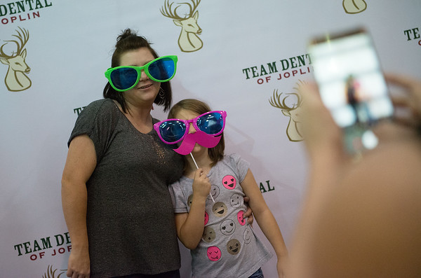 Phoebe, 7, and Christine Boyd, Joplin, pose for a Team Dental of Joplin photobooth on Tuesday during the Joplin Schools Health, Benefits and Retail Therapy Fair at the Memorial Education Center.<br /> Globe | Roger Nomer