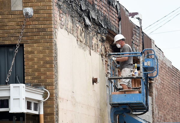 A worker removes part of the old exterior in preparation for what will be the arcade portion of the Decades of Wheels project.<br /> Globe | Laurie SIsk