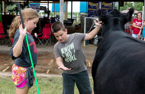 Dylan Young, 10, Fairland, helps Mylie Hance, 10, Fairland, with her showmanship on Friday at the Ottawa County Fair.<br /> Globe | Roger Nomer