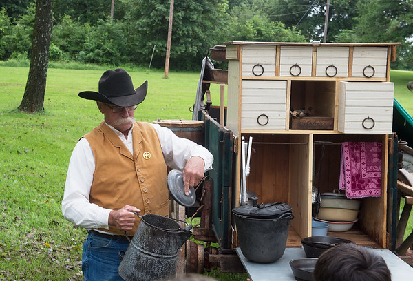 Eldon Bartley talks to Pittsburg students about an important part of frontier life, the coffee pot, on Friday at the Crawford County Historical Society during Little Balkans Days.<br /> Globe | Roger Nomer