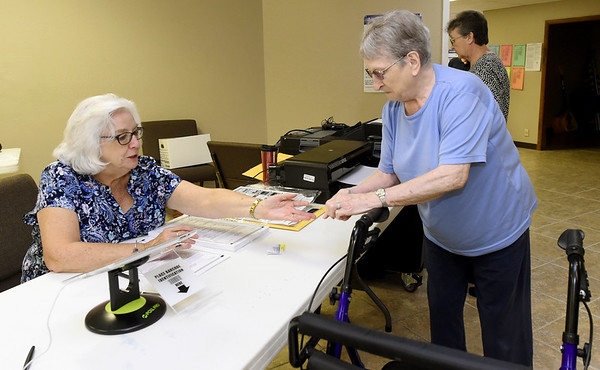 From the left: Election Judge Mary Largent assists Melba Peterson as Peterson prepares to vote in the August primary on Tuesday at Calvary Baptist Church.<br /> Globe | Laurie Sisk