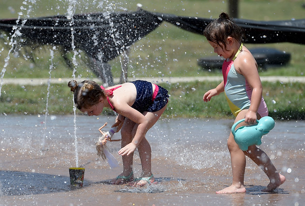 Three-year-old Rosie Trejo, right,  doesn't let the closing of Joplin pools alter her love of water as she makes a new friend in Harlow Hamilton, 4, on Monday at the spray park in Webb City's King Jack Park.<br /> Globe | Laurie Sisk