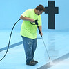 Carthage Parks and Recreation worker Joey Baker pressure washes the floor of the Carthage Pool in preparation for the off-season on Wednesday.<br /> Globe | Laurie Sisk
