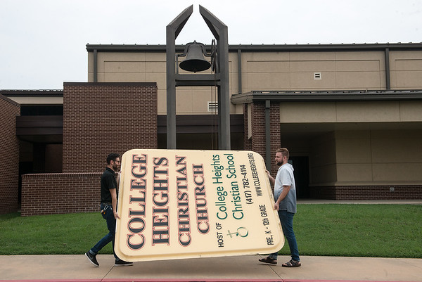 Josh Huckabay, creative arts minister, left, and Ashton Edwards, technical arts manager, carry the former sign of College Heights Christian Church past the Church's original bell on Wednesday.<br /> Globe | Roger Nomer