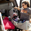 Olathe junior Allison Rangel grabs a load of clothes from her family vehicle as she prepares to move into the Opera House in the Block22 project in downtown Pittsburg on Saturday.<br /> Globe | Laurie Sisk