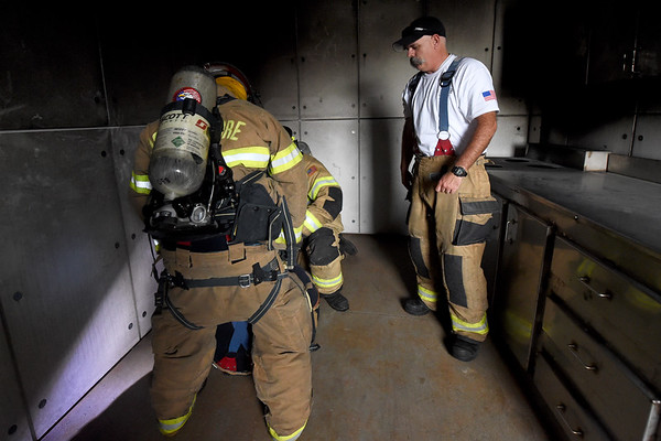 Joplin Fire Department Training Chief Mark Cannon, right, supervises a drill in which firefighters rescue a downed comrade during training drills on Thursday at the Joplin Public Safety Training Center.<br /> Globe | Laurie Sisk