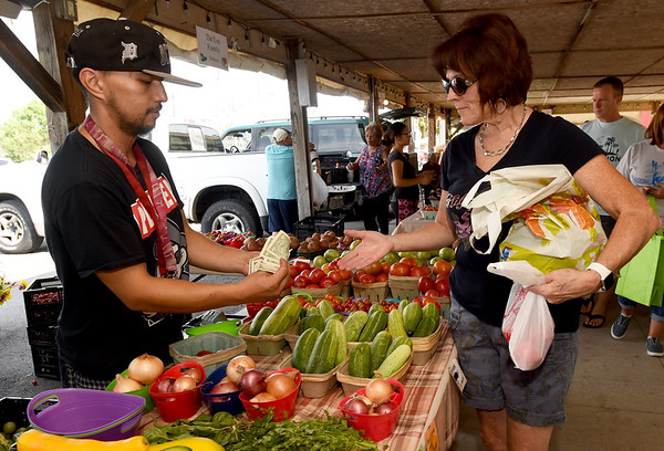 From the left: Gee Vang, of Vang Family Gardens, assists Billie Johnson with a purchase of produce on Saturday at the Webb City Farmers Market.<br /> Globe | Laurie Sisk