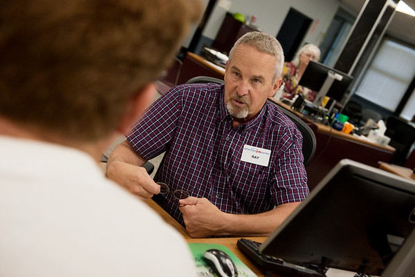 Ray Tupper, left, talks with a client on Thursday at the Joplin Job Center.<br /> Globe | Roger Nomer