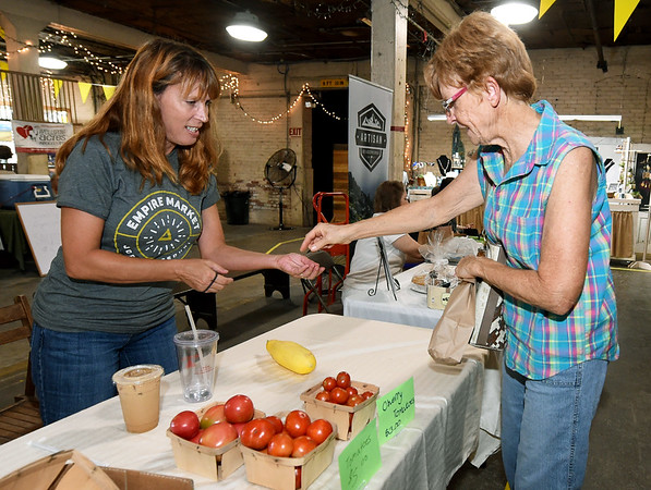 "From the left: Stephanie Gregory, of ""Our Little Piece of Heaven,"" sells some of the last of her produce to Sonja Ledin on Saturday at the Empire Market.<br /> Globe 
