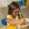 Sofia Rodriguez helps herself to a snack at Midtown Head Start on Wednesday.<br /> Globe | Roger Nomer