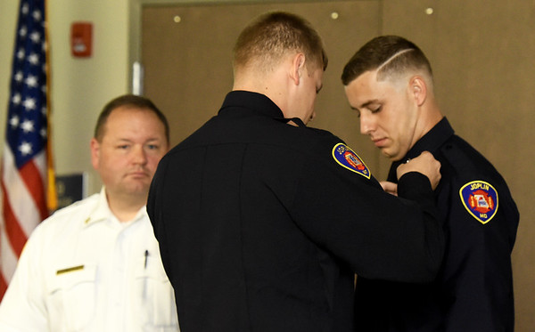 Newly graduated firefighter Dakota Triplett, right,  has his badge pinned upon his shirt by his brother and current firefighter Austin Triplett as Joplin Fire Chief James Furgerson looks on during the Joplin Fire Department Recruit Graduation ceremony on Friday at the Public Safety Training Center. Other graduates include Brad Gillen, Rueben Basaldua, Dakota Harwood, Nicolas Smith, James Hill and Taylor Roberson, who completed training for the Webb City Fire Department.<br /> Globe | Laurie SIsk