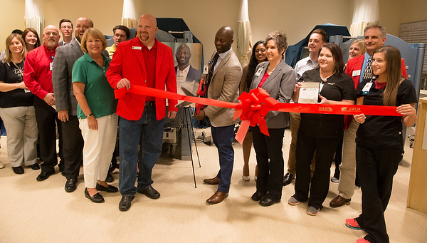 Tobi Yerokun cuts the ribbon for the re-opening of Mercy Wound Care and Hyperbaric Medicine, located at 1905 W. 32nd St., Suite 103, on Wednesday. The outpatient treatment center will focus on treating chronic, non-healing wounds.<br /> Globe | Roger Nomer