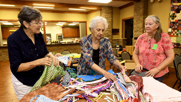 From the left: Carol McCombs, Dorothy Shull and Virginia Gray fold and pack skirts to be shipped to girls in a Haitian orphanage on Thursday at First United Methodist Church in Carthage. The skirts were sewn by about two dozen volunteers.<br /> Globe | Laurie SIsk