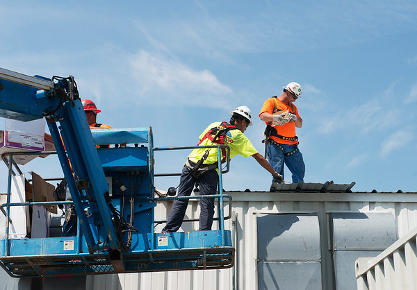 Workers with Mid-Land Enterprises work on the roof of a warehouse at Joplin Workshops on Thursday.<br /> Globe   Roger Nomer