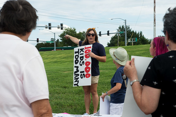 KJ McDonald, southwest Missouri organizer for Missouri Healthcare for All, directs a rally to stop the ongoing purge of eligible Missourians from the Medicaid program on Tuesday at 7th and Range Line Road.<br /> Globe | Roger Nomer