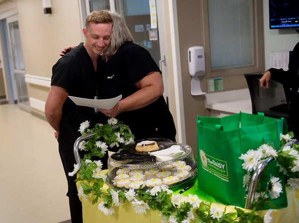 Sam Ward, RN in the Mercy cardiovascular intensive care unit, receives a hug from Becky Tillman, 7 Renal Oncology Clinical Supervisor, as she reads DAISY award nominating statements on Tuesday at Mercy Hospital Joplin. Ward received the DAISY award by being nominated by Tillman and several others.<br /> Globe | Roger Nomer