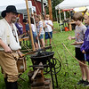 Mike Freund fields questions about his forge from Pittsburg students on Friday at the Crawford County Historical Museum during Little Balkans Days.<br /> Globe | Roger Nomer