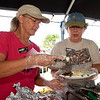 From the left: Sheila Burns and Krista Smith, of the Chert Glades Chapter of the Missouri Master Naturalists, serve biscuits and gravy on Saturday as part of the Webb City Farmers Market's Cooking for a Cause program, which allows organizations a fund raising opportunity.<br /> Globe | Laurie Sisk