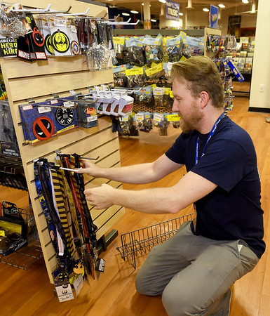Vintage Stock Manager Brandon Bond restocks items on Thursday at his store in Northpark Mall. A proposed use tax aims to level the playing field for brick and mortar stores versus online out-of-state purchases.<br /> Globe | Laurie Sisk