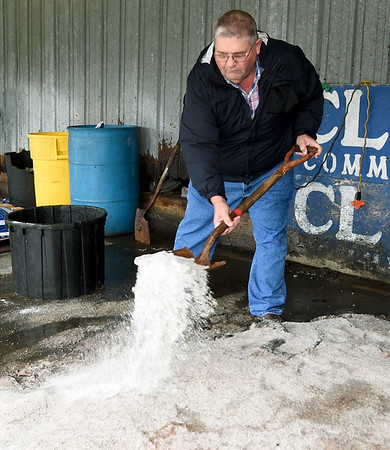 Mike Cloud shovels salt onto cow hides on Thursday at Cloud's Meats. Cloud said he is losing about $2 per hide since tariffs on leather have taken effect.<br /> Globe | Laurie Sisk