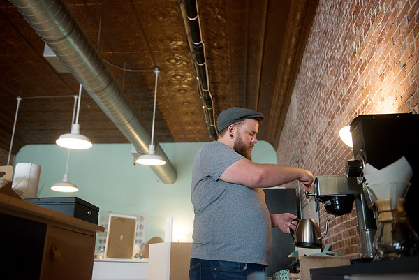 Adam Francis works at his coffee booth on Wednesday afternoon.<br /> Globe | Roger Nomer